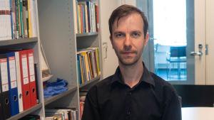 Johannes Kananen i en svart skjorta stående bredvid en bokhylla.