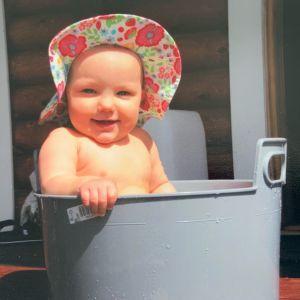 Mari Rosendahlin tytär Nelli hymyilevänä 1-vuotiaana hellehattu päässä istumassa vesisaavissa.