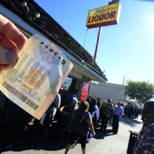 Folk köar för att delta i Powerball-lotteriet. En man visar sin kupong med lottorader.