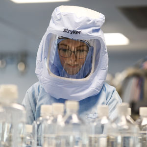 Suojapukuun pukeutunut yöntekijä testaa rokotevalmistuksen prosesseja Biontechin tehtaalla Saksan Marburgissa