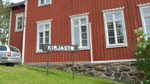 Skylt där det står bibliotek på finska utanför en biblioteksbyggnad.