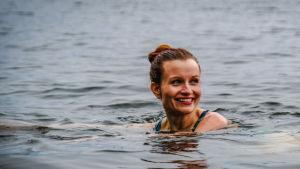 Nainen uimassa järvessä, näkyy vain pää, katsoo hymyillen ohi kameran