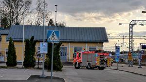 Brandbil framför gul gammal träbyggnad.