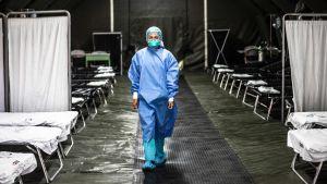 En sjukskötare med blå skyddskläder och munskydd går i en mörk byggnad med tomma sängar.