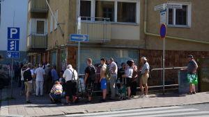 Ett femtiotal personer står i kö längs trottoaren.