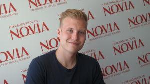 Studerande Arnold Uschanov framför en vägg där det står Yrkeshögskolan Novia