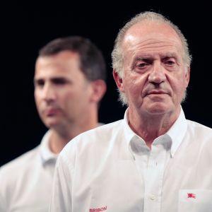 Spaniens tidigare kung Juan Carlos I i bakgrunden syns hans son kung Felipe VI