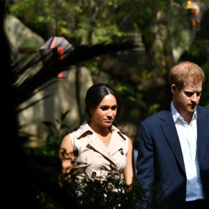 Meghan och prins Harry går bredvid varandra på väg ut ur bild.