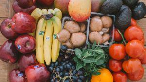 En hög med frukter och grönsaker på ett trägolv.
