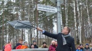 Tom Simola avtäcker John Gardbergsgatans skylt i Karis.