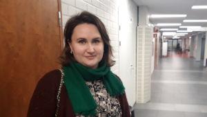 En kvinna står i en skolkorridor och tittar in i kameran.