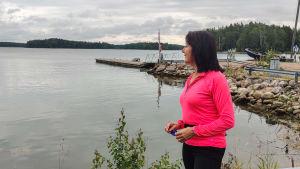En kvinna står och tittar ut på havet.