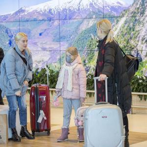 Familj på en flygplats iklädda ansiktsmasker.
