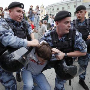 Medlemmar av Rysslands nationalgarde griper demonstranter i Moskva på onsdagen.