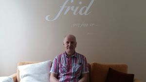 Leif Olin i soffan framför ett bibelcitat på väggen i Sundom Missionskyrka.