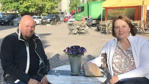 Ett leende par på uteservering på Tölö torg.