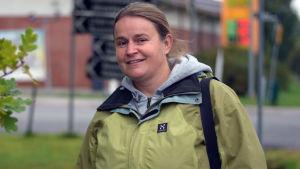 En kvinna med grön jacka står utomhus, framför en market. I bakgrunden ser man också vägskyltar. Hon tittar in kameran.