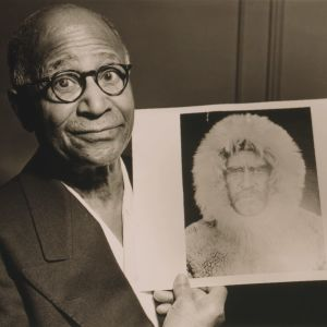 Mustavalkoisessa arkistokuvassa silmälasipäinen tummaihoinen mies puku päällä katsoo kameraan ja pitää kädessään valokuvaa, jossa on turkishuppuiseen takkiin pukeutunut mies