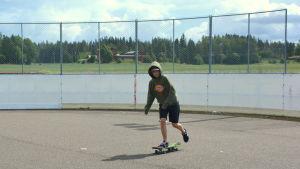 En pojke som åker på en skejtboard inne i en rink.