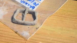 Ett litet medeltida bronsspänne i en plastpåse med text på. Ett fynd vid arkeologiska utgrävningar på Slottsmalmen vid Raseborgs slott sommaren 2018.