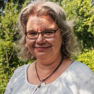 Kvinna i vit linneskjorta, ljust hår och glasögon i trädgård.