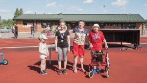 Neljä eri-ikäistä naista seisoo rivissä urheilukentällä hymyillen ja mitalit kaulassa.