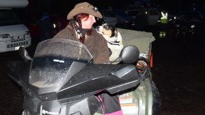 En kvinna i hatt och en hund på en fyrhjuling. Det är mörkt som på natten ute.