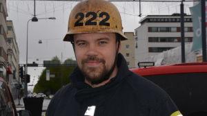 Mansperson iklädd brandmanskläder och hjälm ser in i kameran.