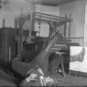 """Två män leker """"bryta stubbar"""". Bilden är tagen 1935 i Bromarf, Rilaks."""