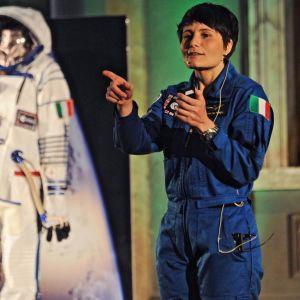 En kvinna klädd i mörkblå overall pekar med ena handen. Till vänster om henne finns en vit rymddräkt.