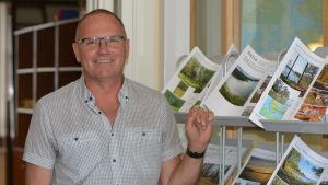 en man inne i en fastighetsförmedling med broschyrer över bostadsobjekt som är till salu i bakgrunden.