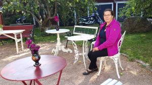 Porträttfoto av Anette Kanteh som sitter vid ett gammaldags trädgårdsbord i en trädgård.