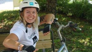 Malin Valtonen sitter med cykelhjälm på huvudet vid en cykel.