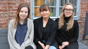 Ellen Wilenius, Julia Nummenmaa och Catharina Walldén sitter på en bänk