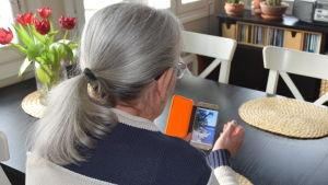 En kvinna sitter vid ett köksbord med ryggen mot fotografen. Hon tittar på ett fotografi i sin mobiltelefon