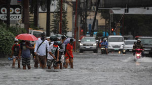 Människor i vattenmassor i samband med översvämning i Makati, Filippinerna