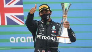 Lewis Hamilton visar tummen upp me pokalen i ena handen.