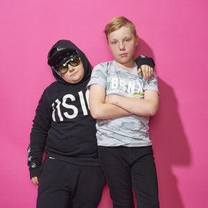 Melvin poserar med solglasögon, keps och huva på huvudet. Oliver står med armarna i kors. Melvin håller sin vänstra arm på Olivers vänstra axel.
