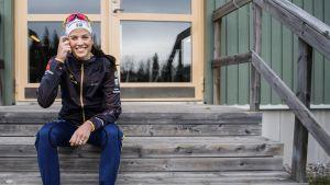 Anna Dyvik sitter på en trappa och ler.