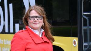 Kollektivtrafikchef Sirpa Korte står i röd jacka framför den gula Fölibussen.