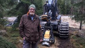 En man står i en skog framför en skogsmaskin.