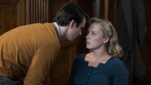 Närbild på Joan (Annie Starke) då hon sitter på en stol och Joe (Harry Lloyd) böjer sig över henne för att förklara vad han menar.