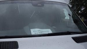 """En silverfärgad minibuss med en lapp i framrutan där det står """"Byabussen-Kyläbussi""""."""