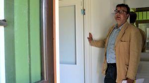 Man i skjorta oc kavaj står i dörröppningen till en grön träbyggnad.