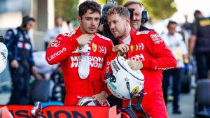 Leclerc och Vettel står bakom en Ferarribil och talar med varandra.