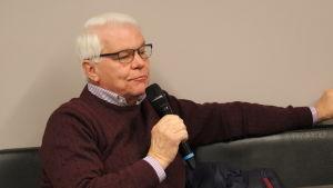 En gråhårig man med en mikrofon i handen.