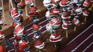 Jordgubbar och blåbär påträdda på pinnar, med vitchoklad som har ringlats över.