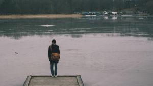 Person står på ändan av en brygga.