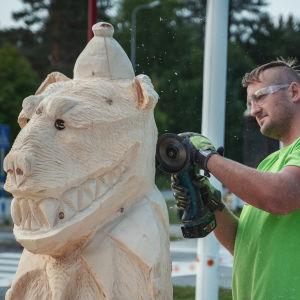 Mies suojalasit päässä hioo kulmahiomakoneella karhun mallista puuveistosta