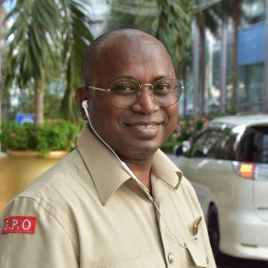 En man i glasögon med en öronsnäcka ler in i kameran.